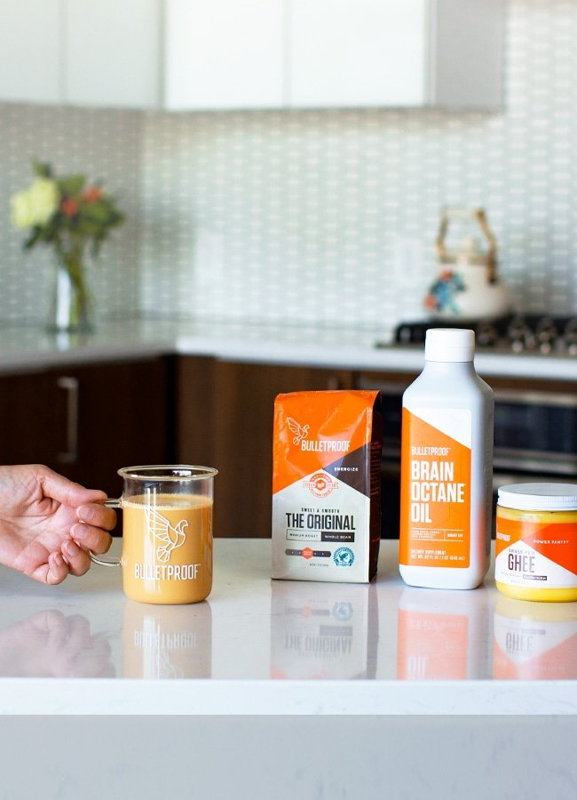 coffee cup, ground cofee, octane oil, and ghee on counter top