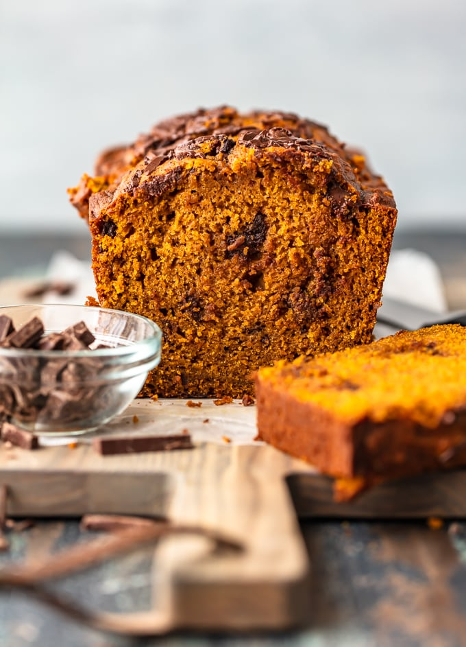 Chocolate chunk pumpkin bread on a cutting board, next to a bowl of chocolate chunks