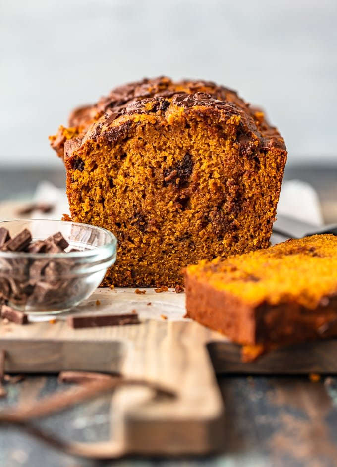 Chocolate chunk pumpkin bread on a cutting board, next to a bowl of chocolate chunks