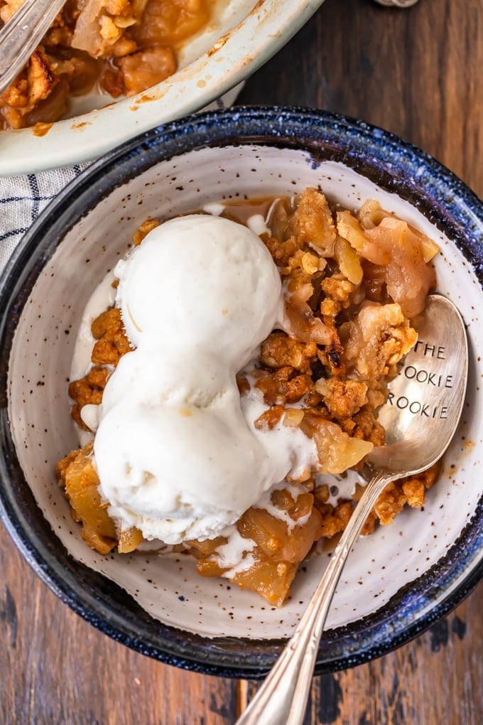 A bowl filled with fresh apple crisp topped with ice cream