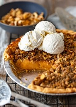 homemade sweet potato pie in a dish topped with scoops of vanilla ice cream