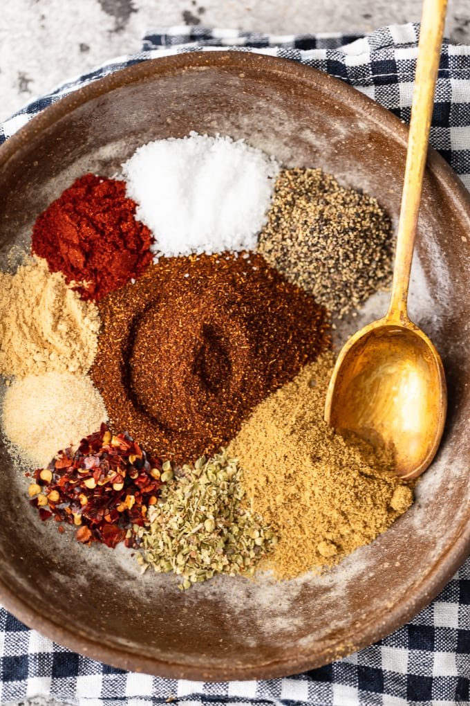 A bowl full of spices with a gold spoon