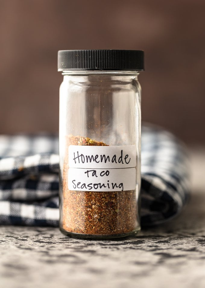 A glass spice jar filled with homemade taco seasoning