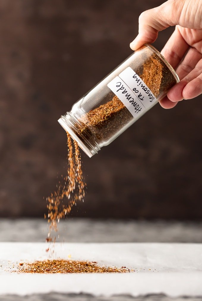 Pouring taco seasoning out of a glass jar