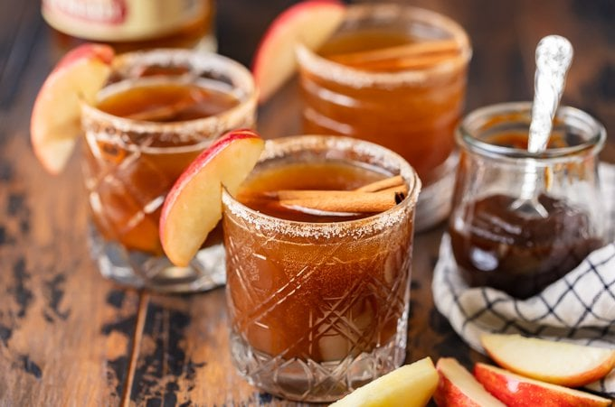 3 apple old fashioneds in glasses garnished with apple and cinnamon