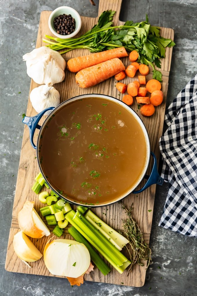 How to make chicken broth: carrots, celery, and garlic sit on a cutting board, next to a pot of chicken broth