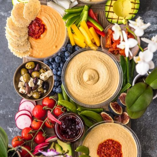 The Ultimate Hummus and Vegetable Board is easier to throw together than you might think! This beautiful spread of Hummus, Summer Veggies, and more is sure to please even the pickiest crowd, and it's healthy as well! So much flavor on this Hummus Board!