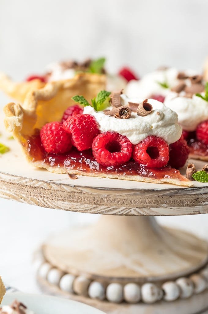 Raspberry tart topped with whipped cream, chocolate shavings, and mint