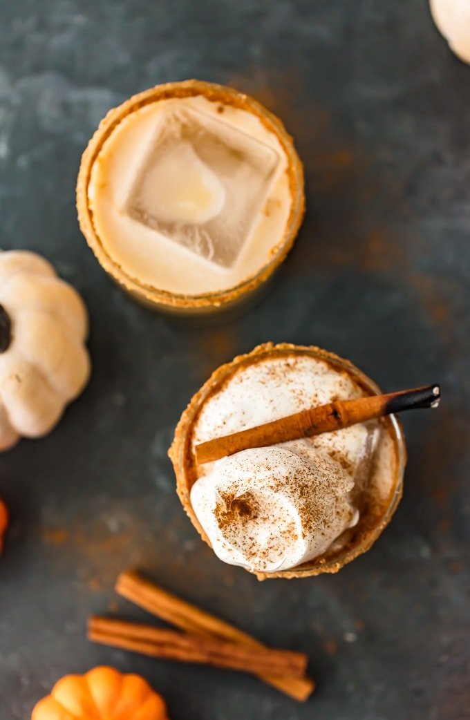 Two Pumpkin Spice White Russian cocktails viewed from above, one with an ice cube and the other topped with whipped cream
