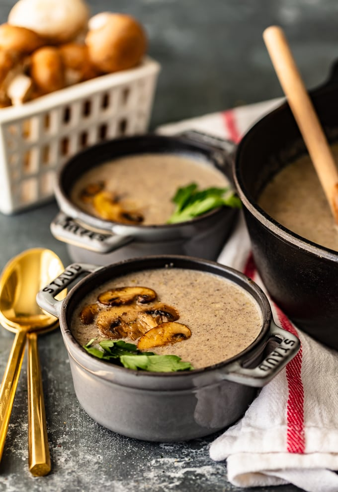 Two bowls of cream of mushroom soup next to a large pot of soup and a basket of mushrooms