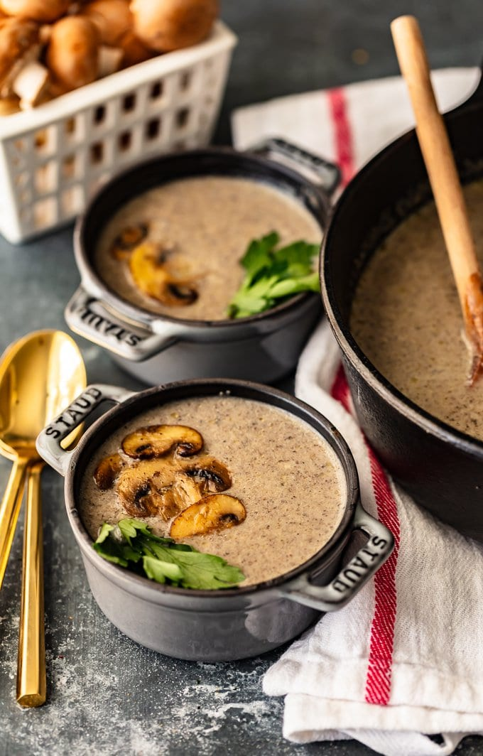 Two bowls of cream of mushroom soup topped with sliced mushrooms