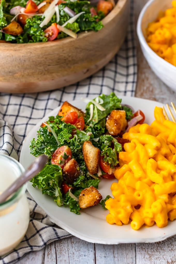 A white plate with mac and cheese and a kale caesar salad