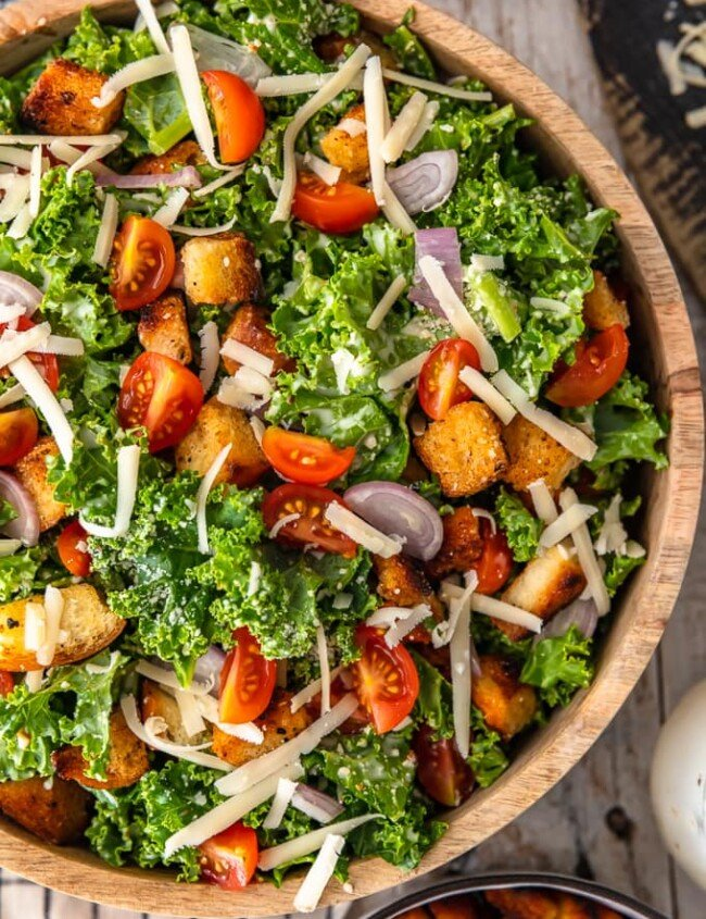 Kale Caesar Salad is the perfect side salad for any meal! It's just like a classic caesar salad, but with a twist. You've got the homemade croutons and the caesar dressing, but we're throwing in kale instead of romaine, and adding some tomatoes and shallots for extra flavor. This salad recipe is good!