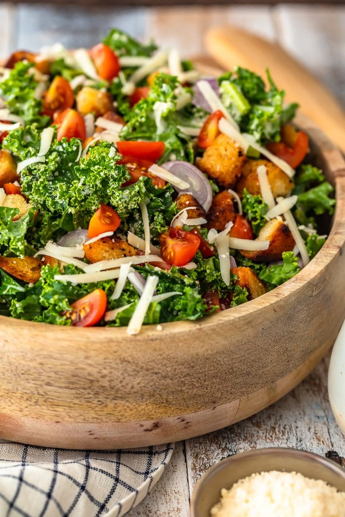 A bowl of kale caesar salad topped with cheese, croutons, tomatoes, and shallots