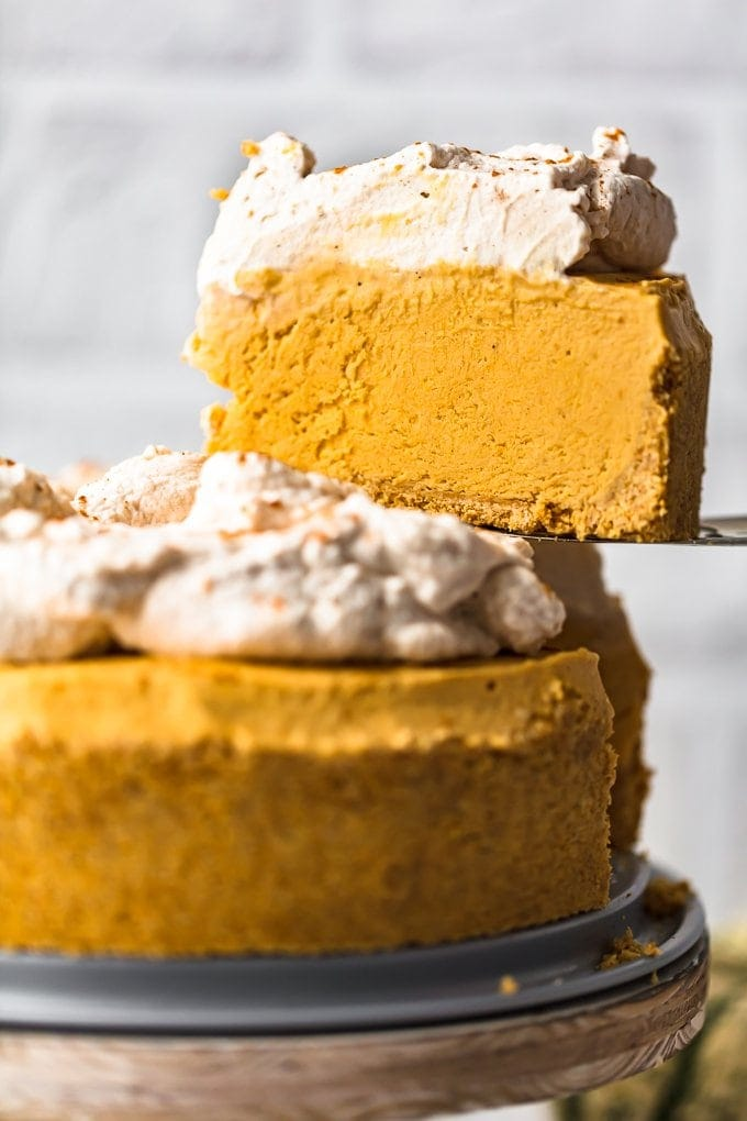 A slice of pumpkin pie cheesecake held above a whole cheesecake