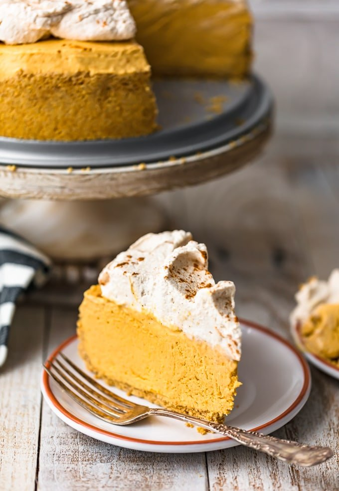 A slice of pumpkin cheesecake on a small plate, topped with whipped cream