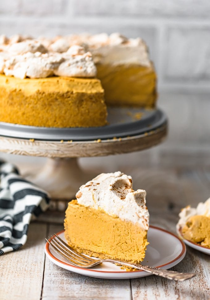 A no bake pumpkin cheesecake on a cake stand, with a slice of cheesecake on a small plate in front