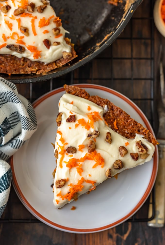 a triangular slice of carrot cake on a small white plate