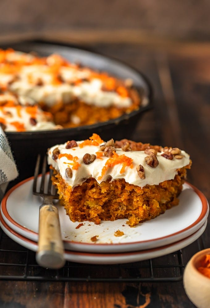 A slice of carrot cake on a plate, with a skillet carrot cake recipe in the bacground