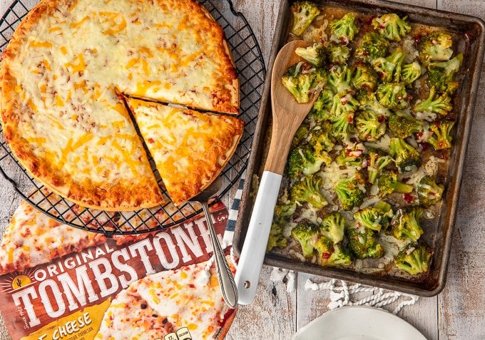 cheese pizza on wire rack next to a sheet pan of spicy cheesy broccoli