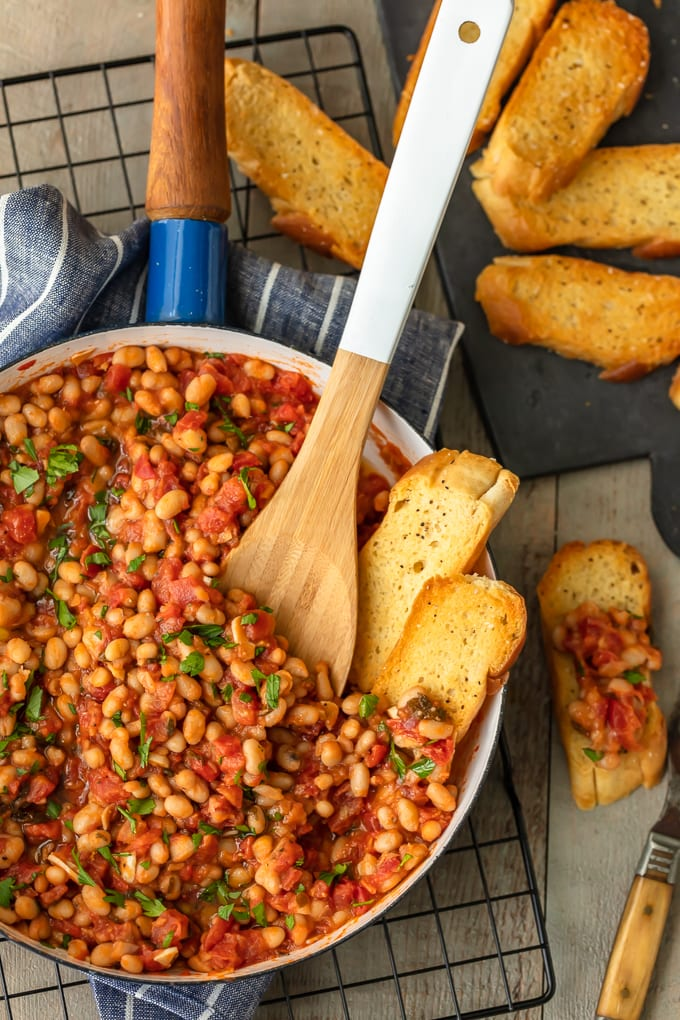 white beans and tomatoes in a skillet, surrounded by pieces of bread