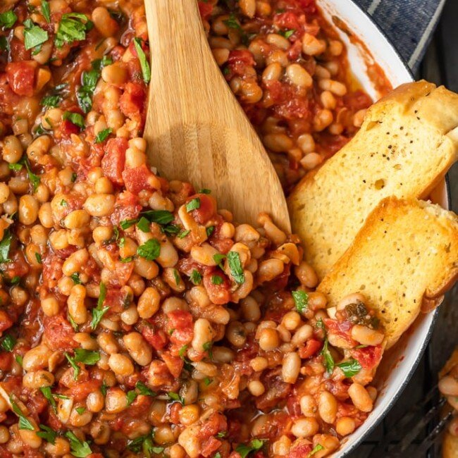 This White Beans recipe is so simple, yet so delicious! Cannellini beans cooked with tomatoes, garlic, and chicken broth make for one tasty side dish. It's perfect for holidays or easy weeknight meals!