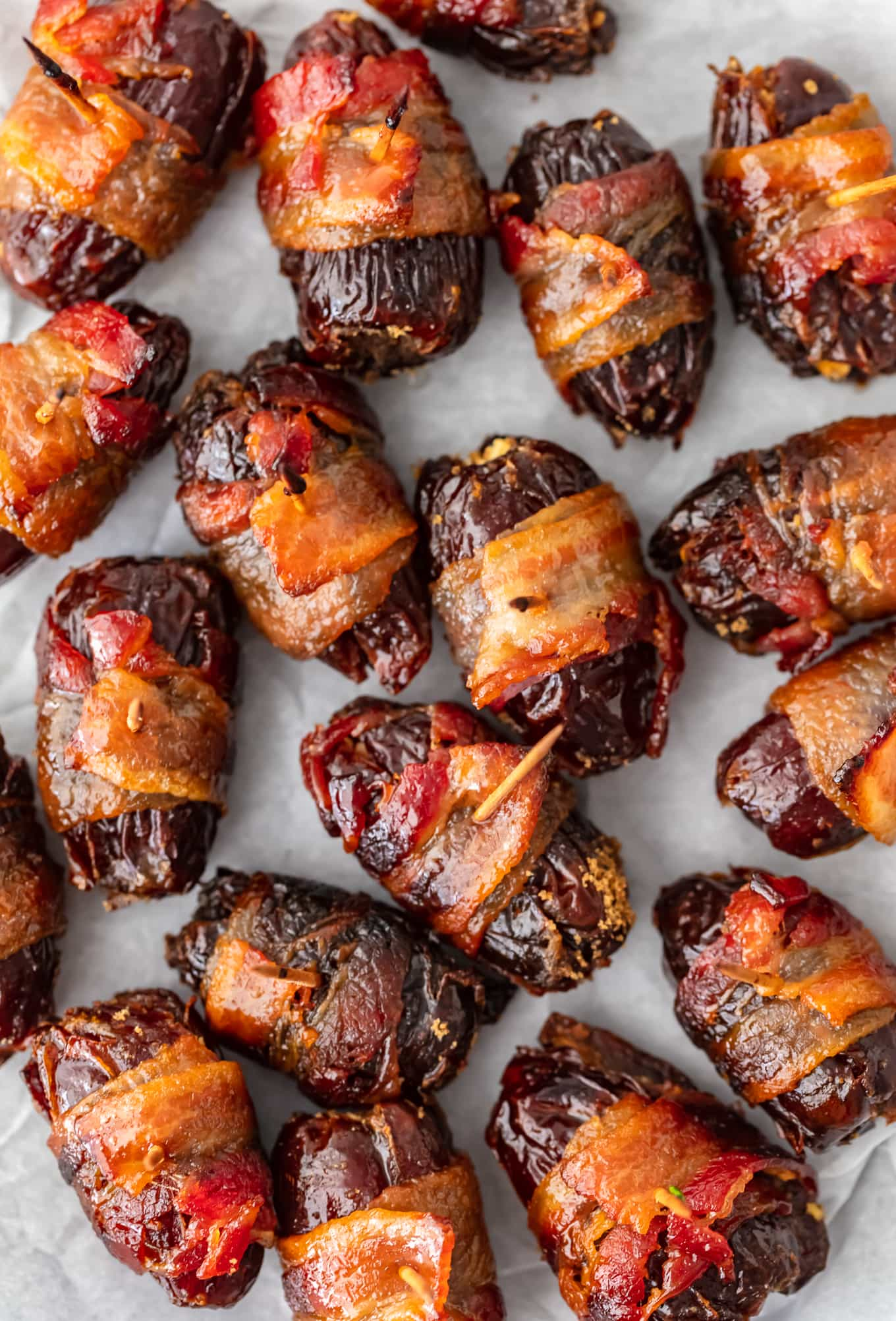 bacon wrapped dates arranged on parchment paper