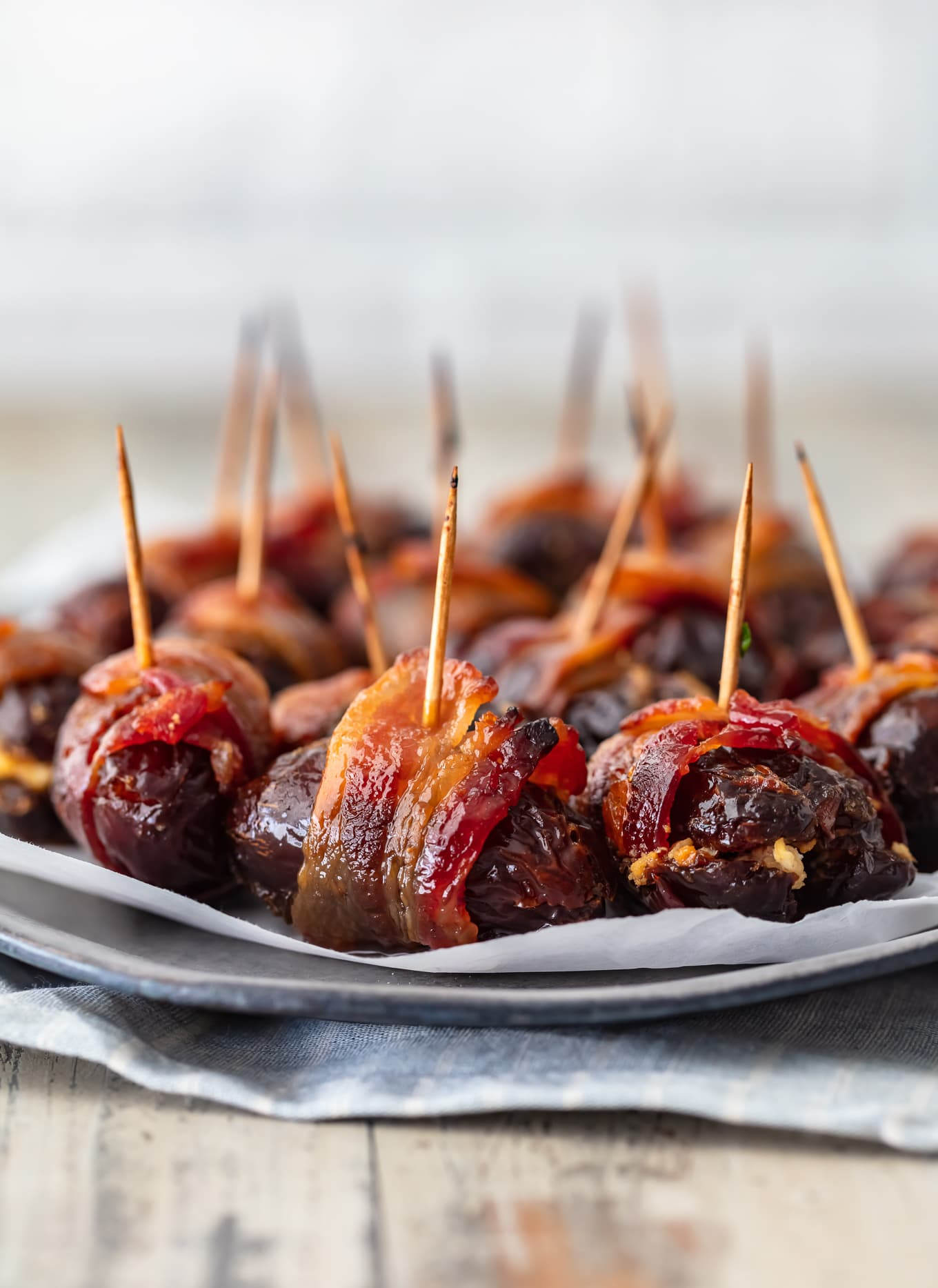 a plate of dates wrapped in bacon with toothpicks