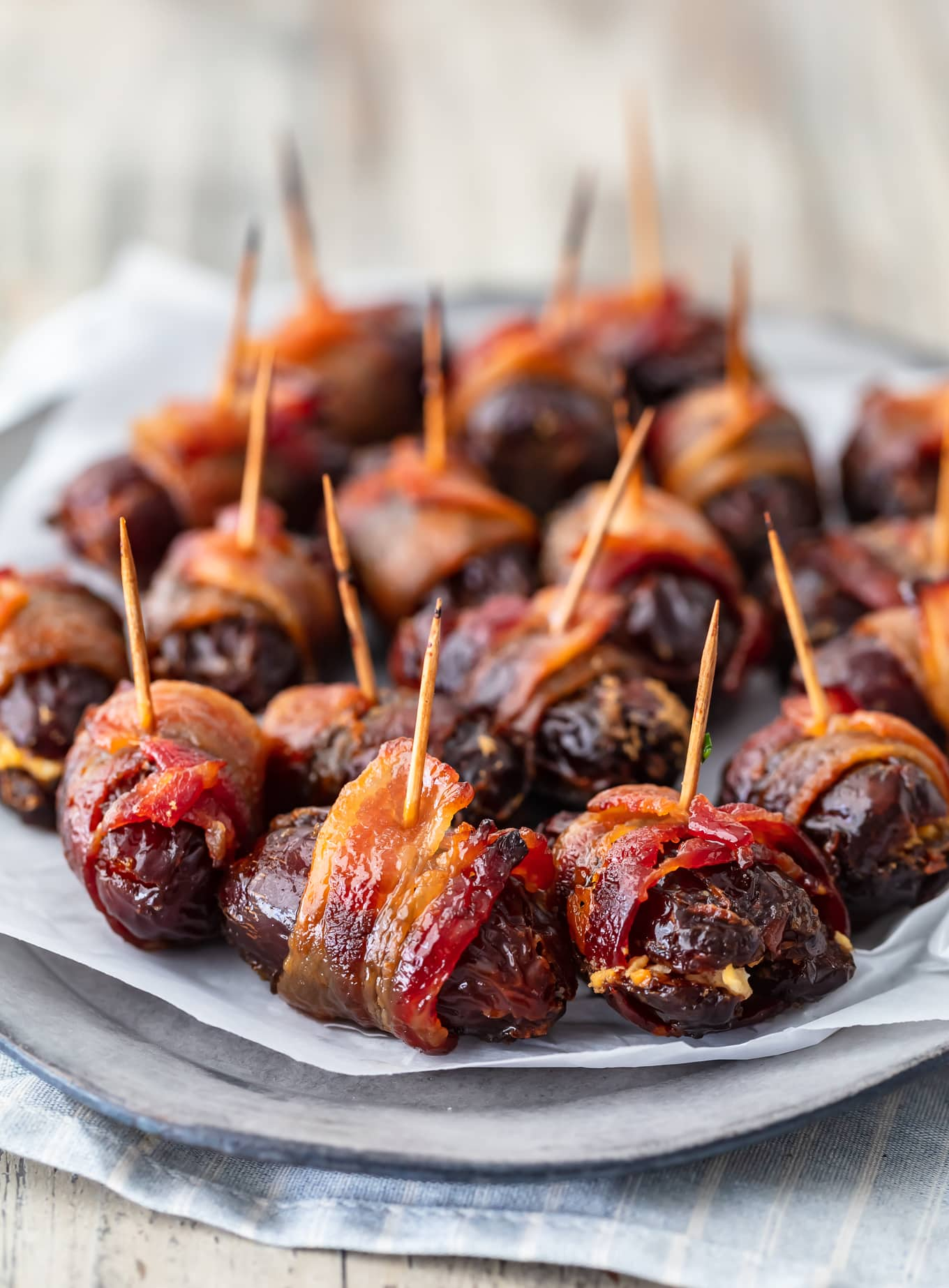 bacon wrapped dates on a serving plate covered with parchment paper