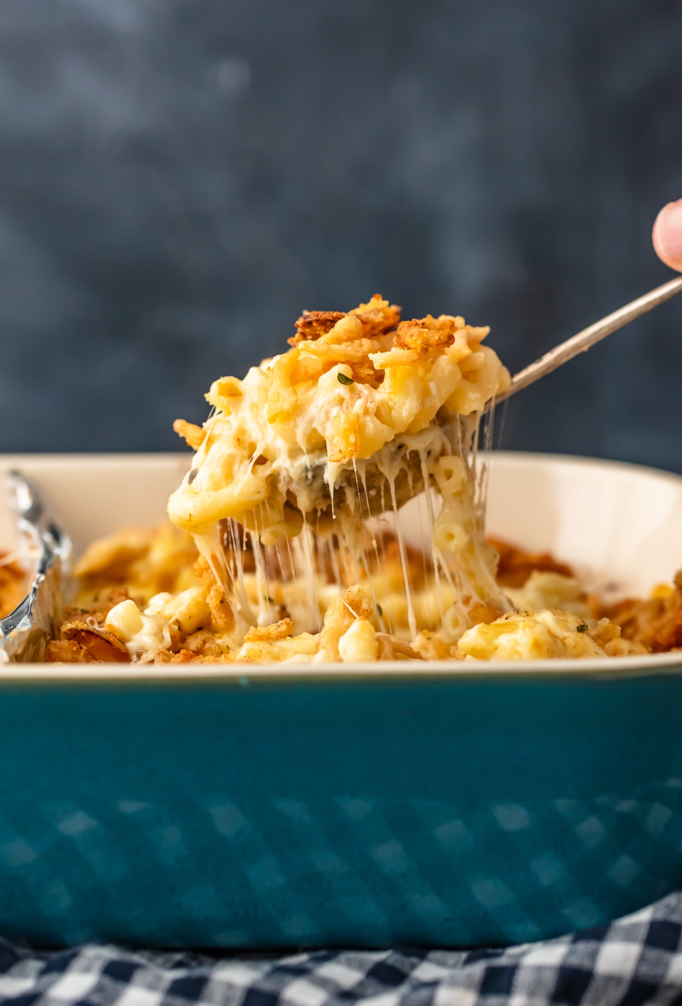 lifting up a spoonful of cheesy baked macaroni and cheese casserole