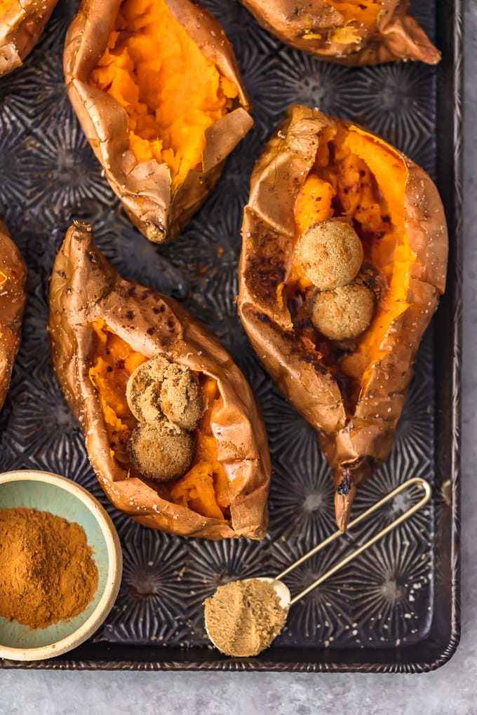 baked sweet potatoes on a baking tray, filled with brown sugar and cinnamon