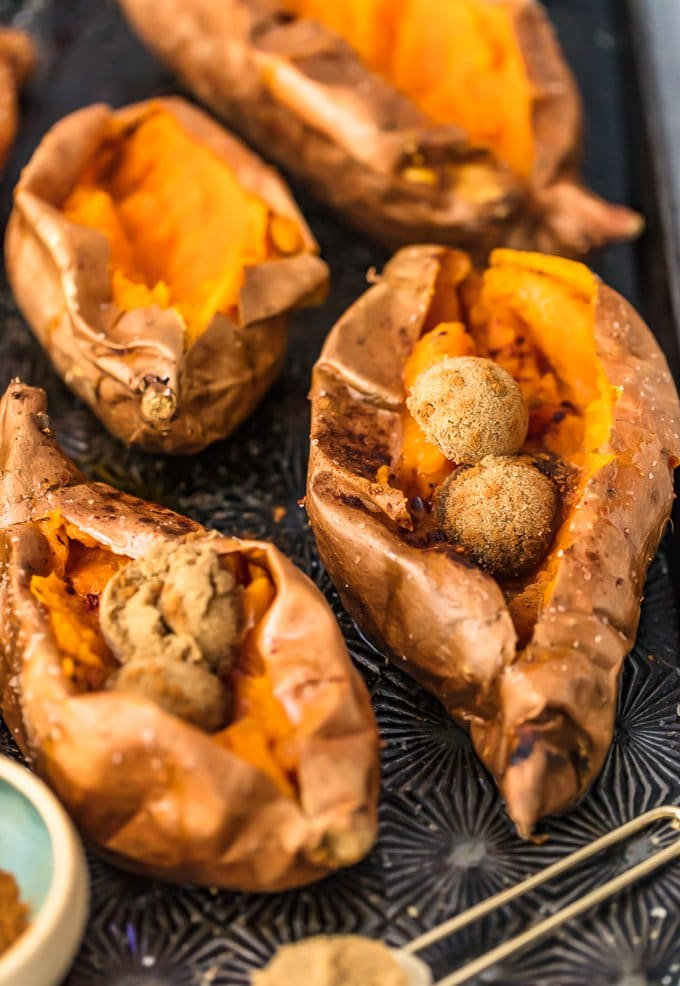 four baked sweet potatoes on a baking tray
