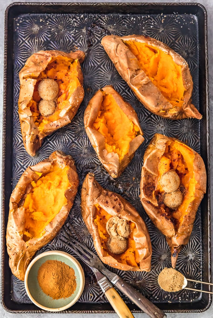 baked sweet potatoes sliced open, arranged on a baking sheet