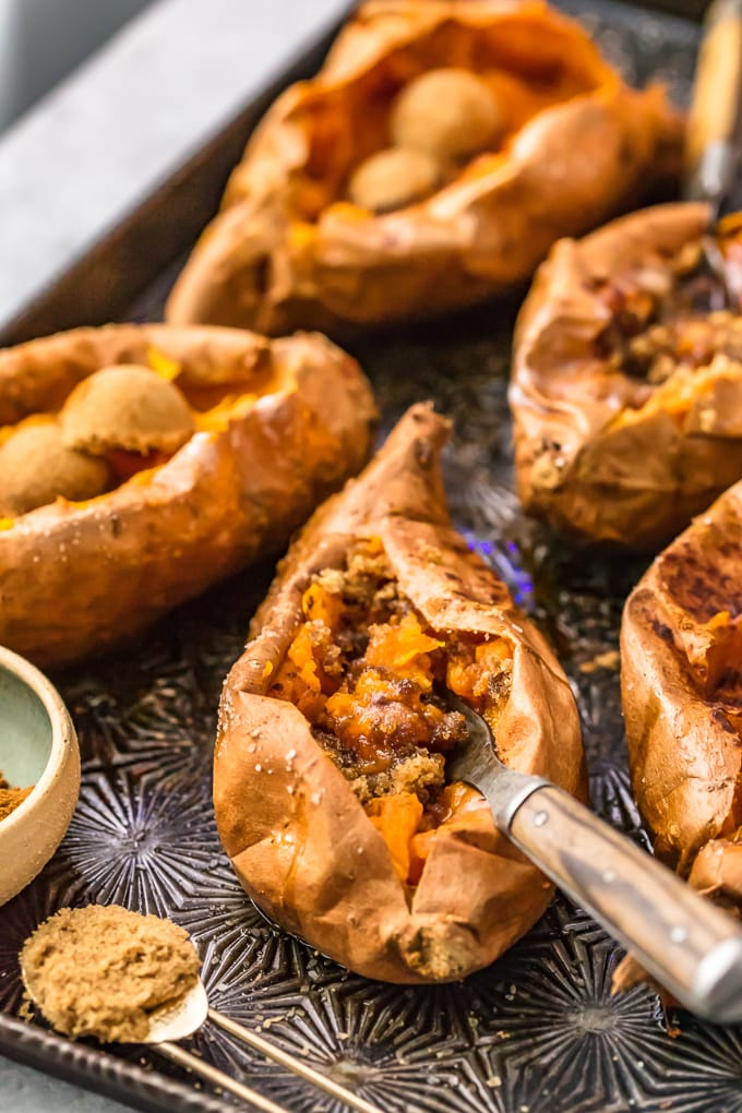 sweet potatoes on a baking sheet, stuffed with brown sugar and cinnamon