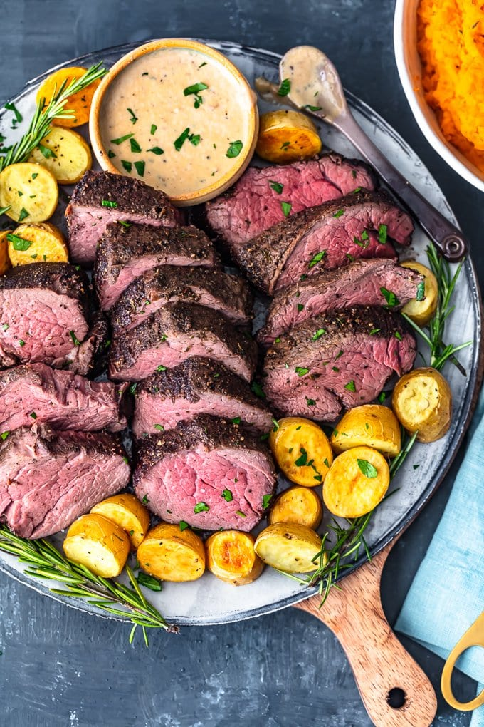 the best beef tenderloin recipe on a plate with brandy cream sauce and potatoes