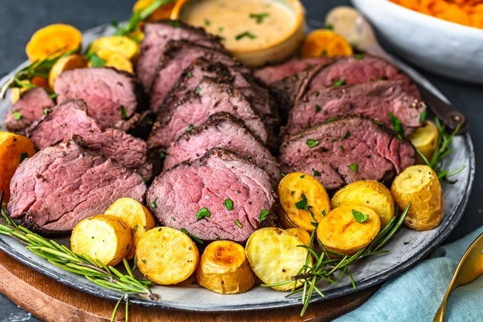 a plate of sliced beef tenderloin with potatoes