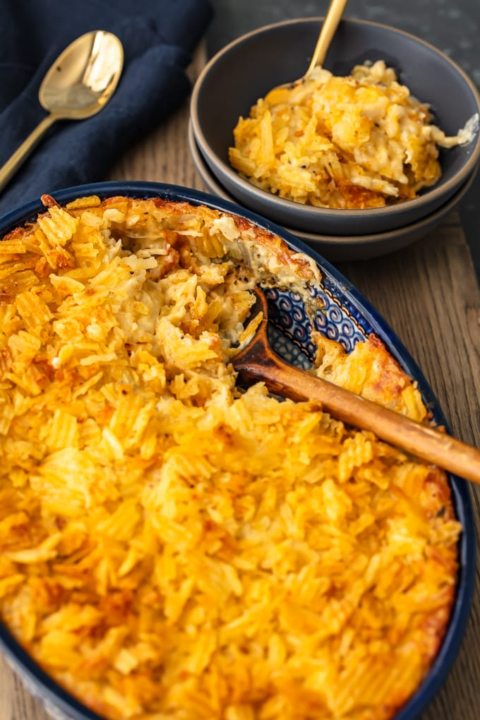 cheesy potato casserole in a blue casserole dish next to a bowl of cheesy potatoes