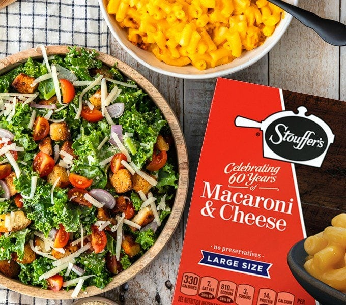 kale salad in a bowl next to a box and bowl of stouffer's macaroni and cheese