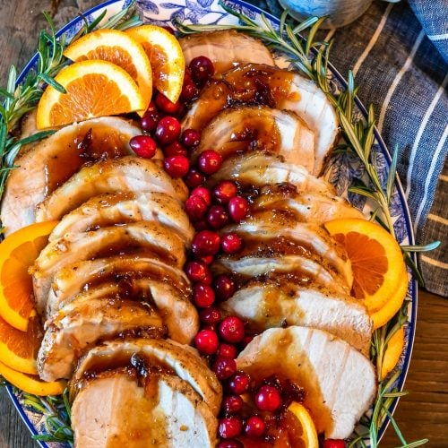 This Pork Loin Roast recipe is the perfect holiday main dish! This Orange Cranberry Pork Loin Roast is juicy, delicious, and super festive. Add this roasted pork recipe to your Thanksgiving and Christmas tables!