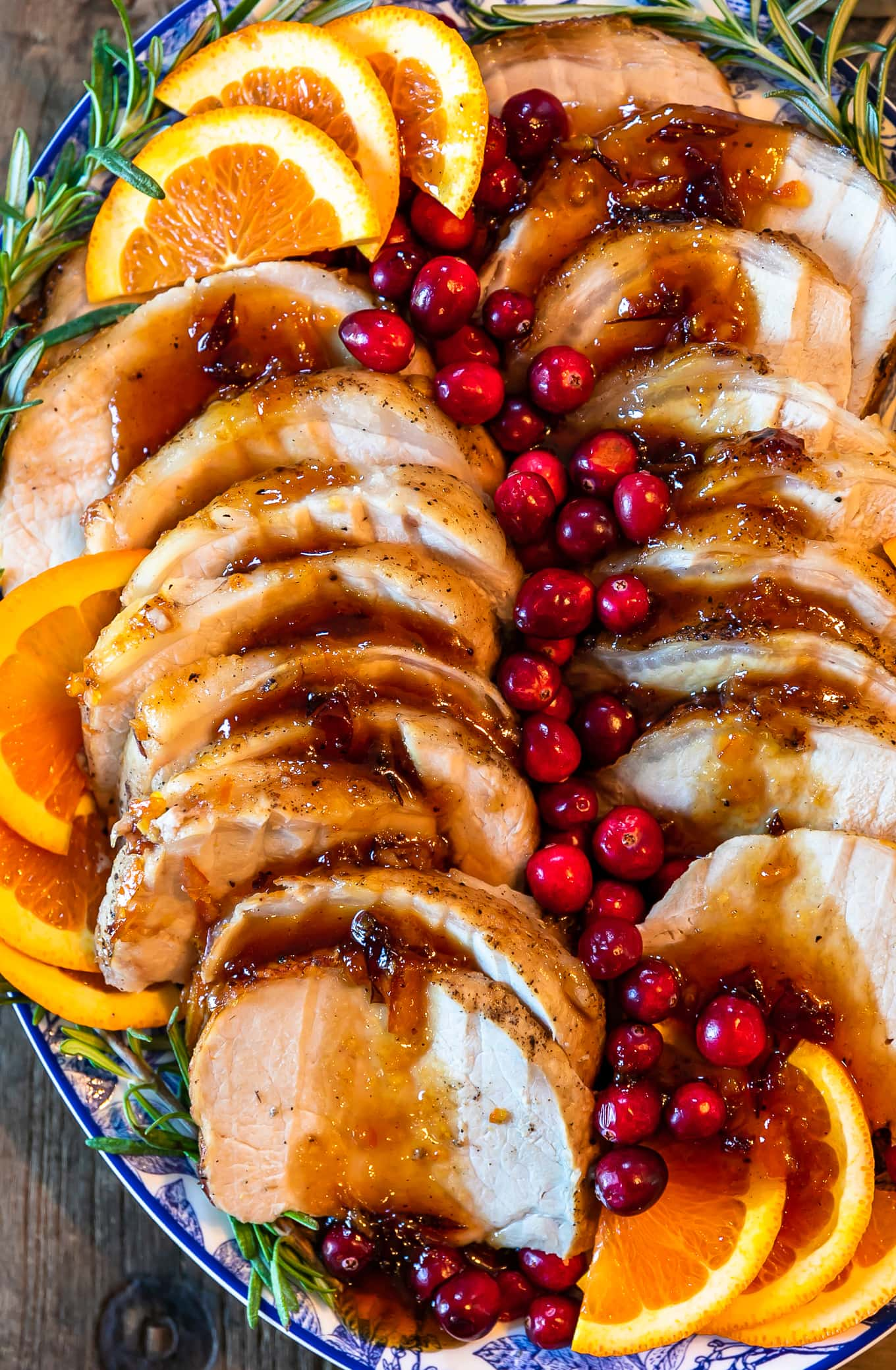 close up of pork loin roast recipe covered in an orange cranberry sauce, and fresh cranberries and orange slices