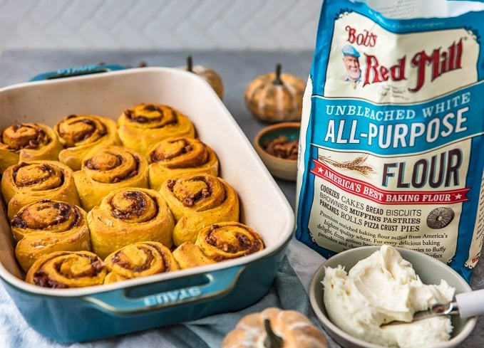 pumpkin cinnamon rolls in a baking dish, next to a bag of flour