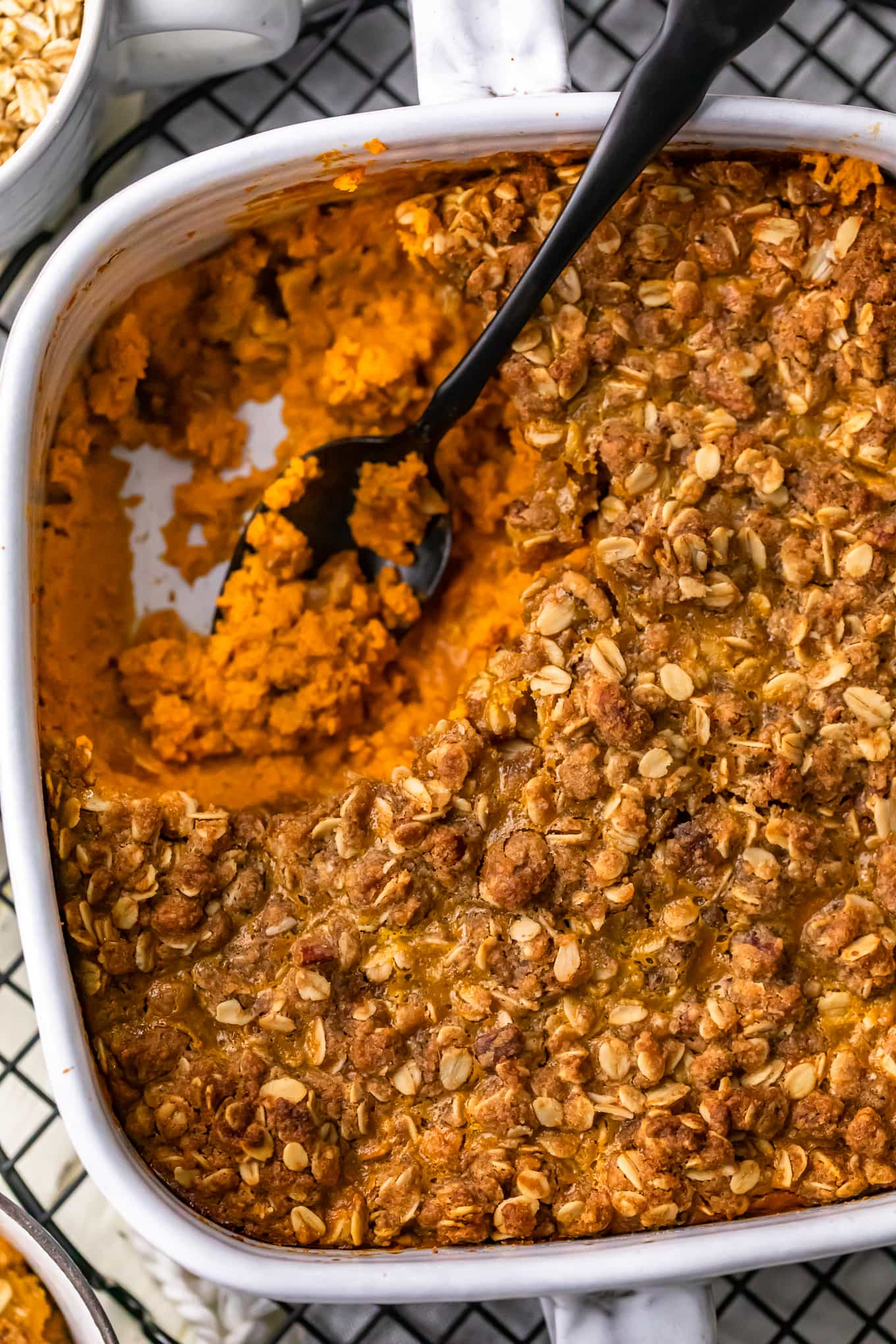 overhead view of pumpkin pie crumble in a white backing dish, with a portion of it removed
