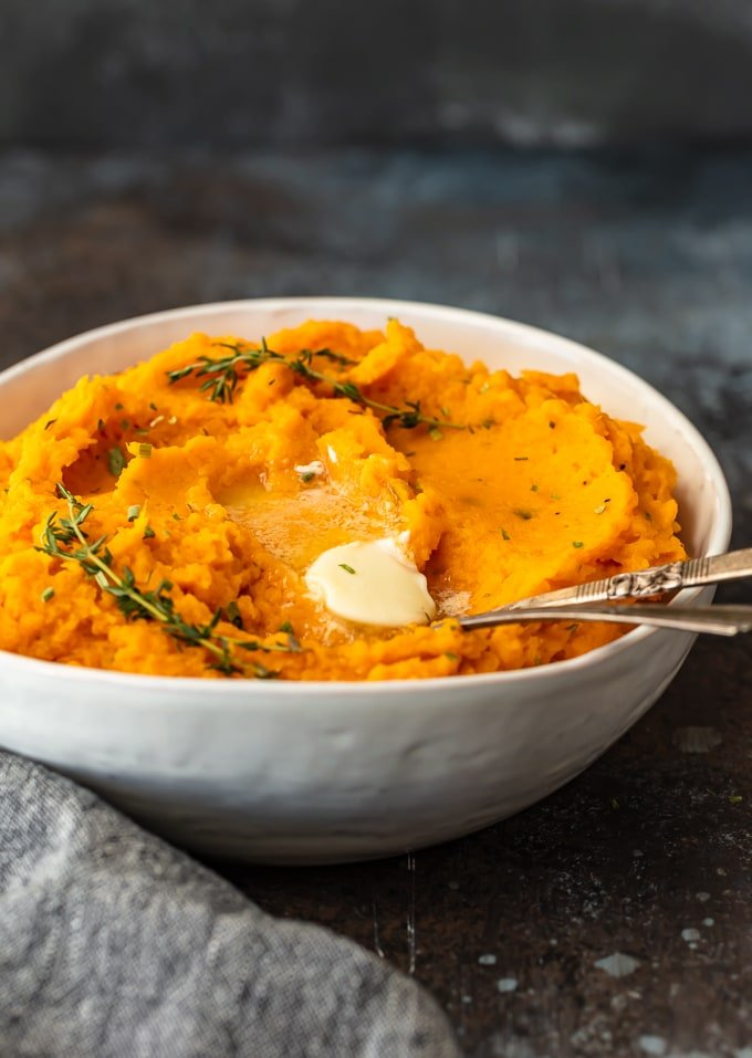 savory mashed sweet potatoes in a white bowl with a spoon