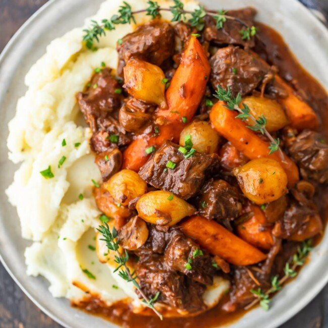 Beef Bourguignon is a delicious beef stew that's perfect for winter meals. Also known as beef burgundy or boeuf bourguignon, this dish is hearty and filling. This beef bourguignon recipe is made with beef, red wine, beef broth, and lots of vegetables. Serve this beef burgundy stew with mashed potatoes, egg noodles, rice, or all on its own. It's delicious no matter what!