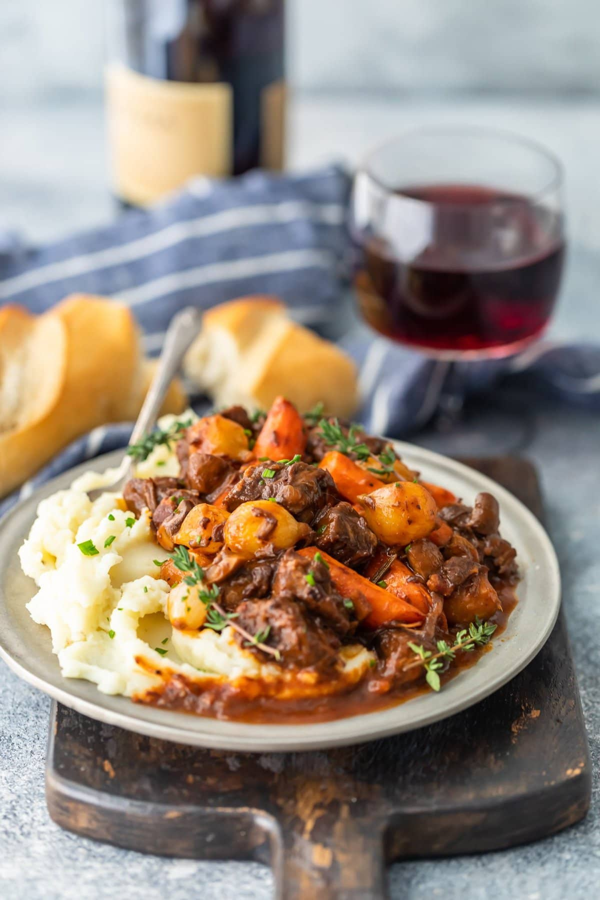 a plate of boeuf bourguignon next to a glass of red wine
