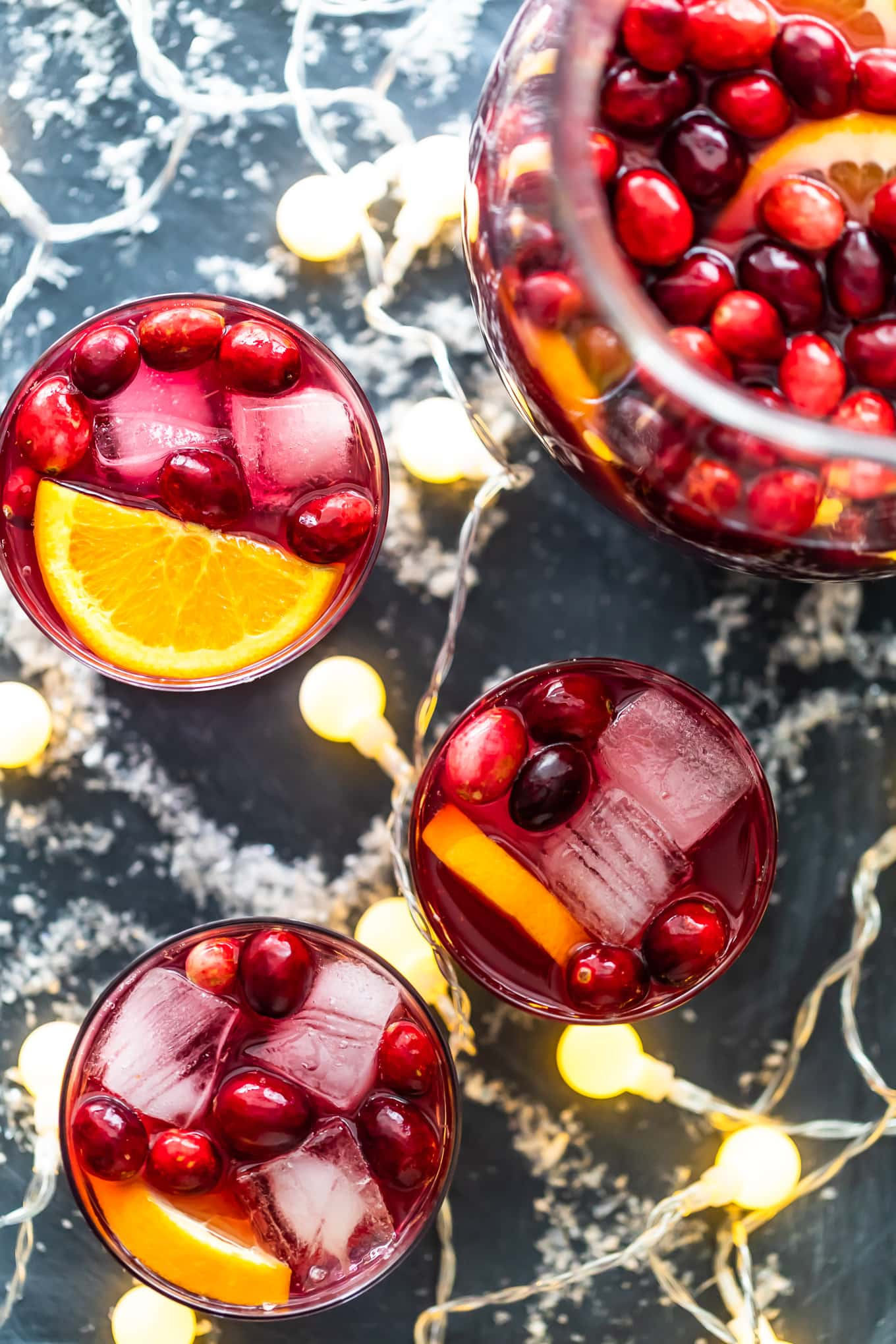 overhead view of sangria topped with cranberries and orange slices