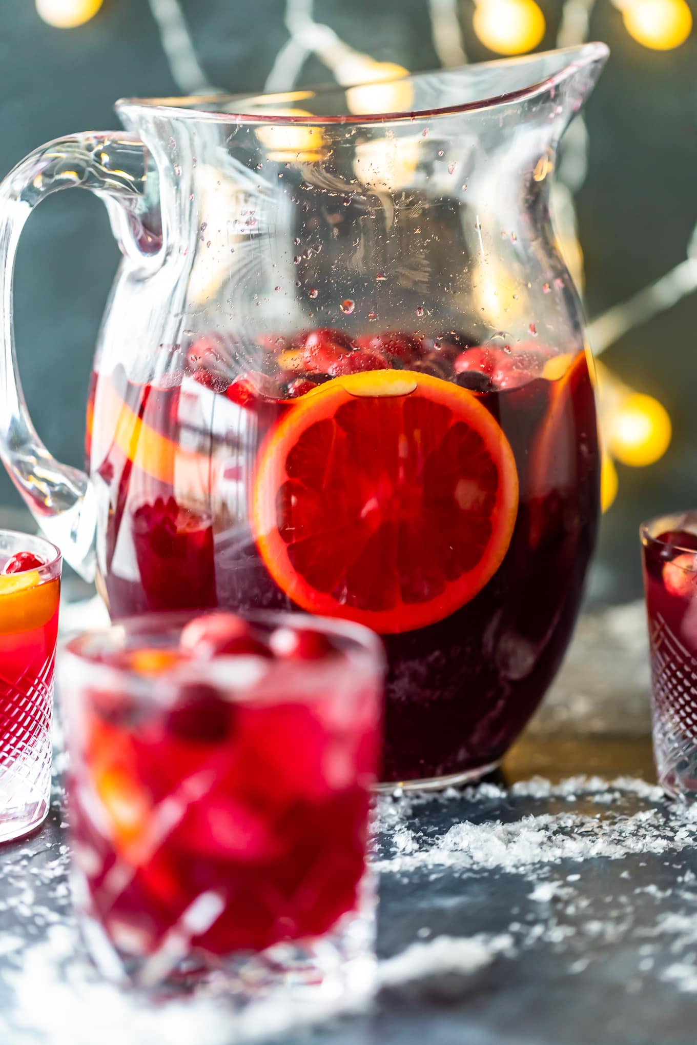 orange cranberry sangria in a pitcher, surrounded by glasses of sangria