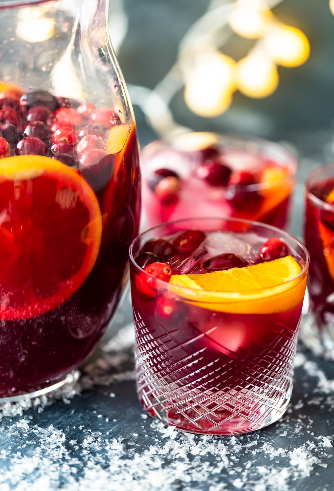 a pitcher of orange cranberry sangria next to glasses