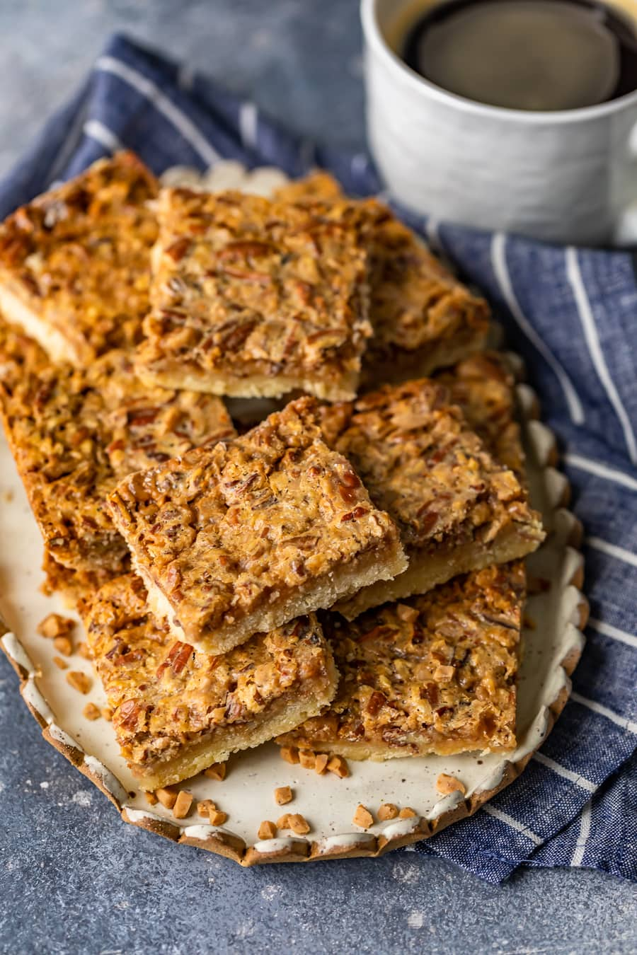 a plate of pecan bars sitting on a blue and white striped dish towel