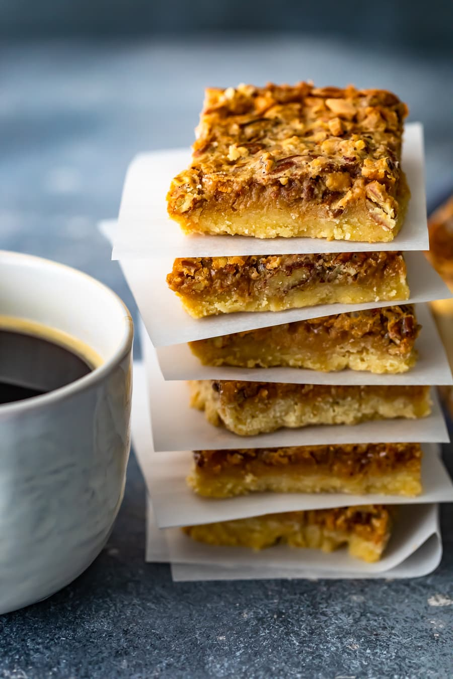 a stack of pecan pie bars with sheets of parchment paper between each one